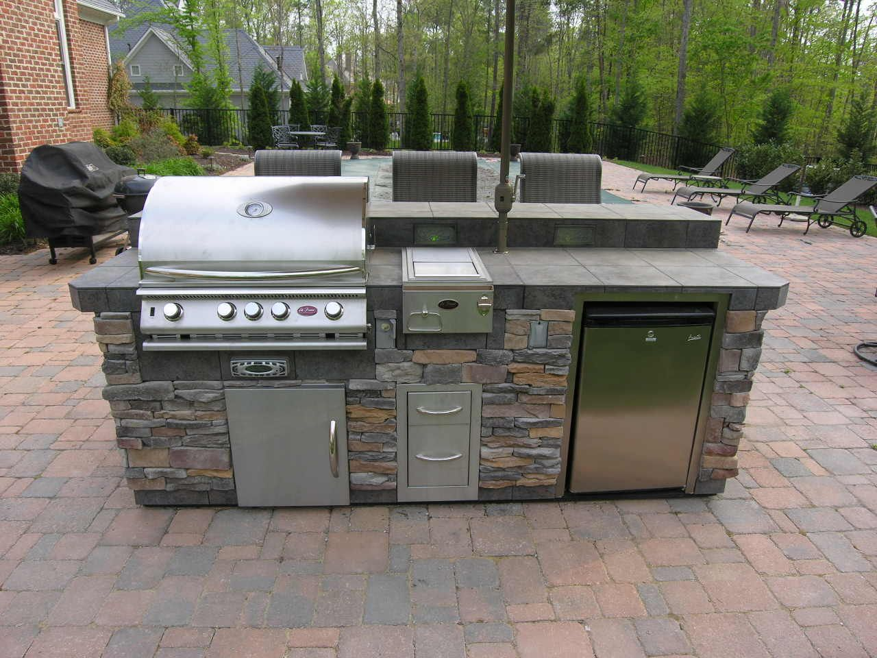 Straight Outdoor Kitchen In Natural Stone Overlooking The Backyard S Pool Area This Cu Modular Outdoor Kitchens Outdoor Kitchen Island Prefab Outdoor Kitchen