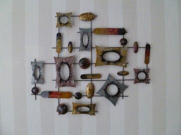 een groot metalen object als kunststuk aan de muur. | kunstmuur, Deco ideeën