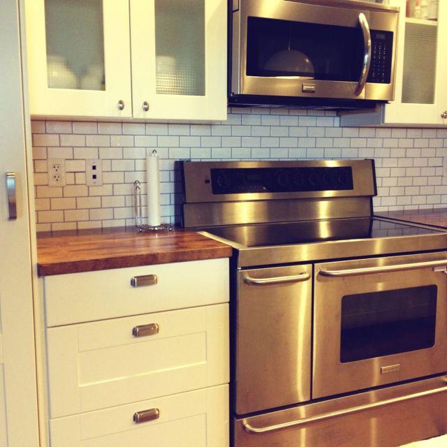 2x4 White Subway Tile Backsplash Cup Drawer Pulls Butcher Block Countertops Stainless Steel White Modern Kitchen White Kitchen Farmhouse Sink Kitchen Decor