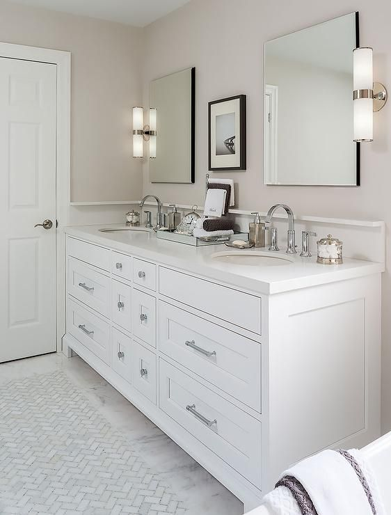 White and tan bathroom features a white dual sink vanity topped ...