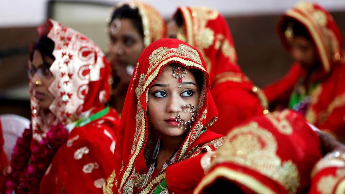 Un grupo de novias esperan sentadas su turno durante una boda masiva musulmana en Ahmedabad (India).
