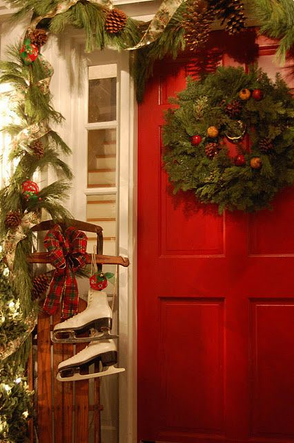 Porch all decorated for Christmas... ice skates, sled, greenery, wreath, pine cones, garland