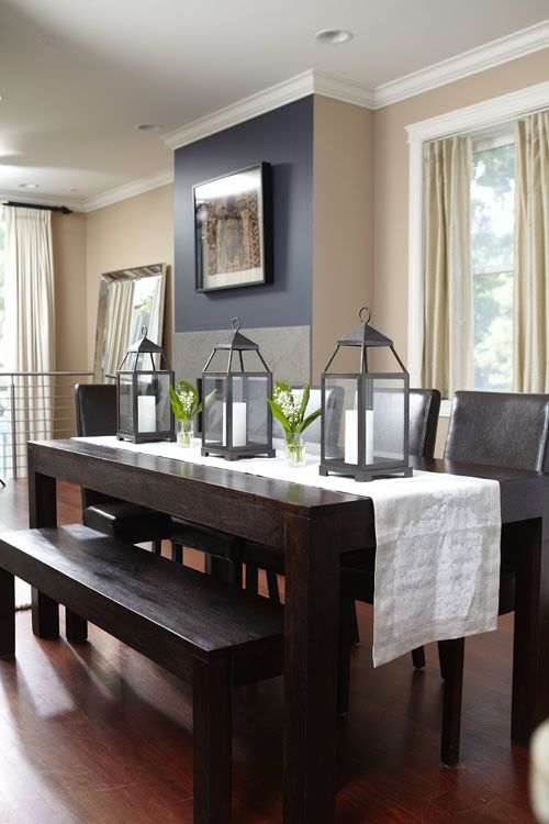 Dining table with runner and industrial lamps. Hint of green with plants. Neutral wall colors to offset room.