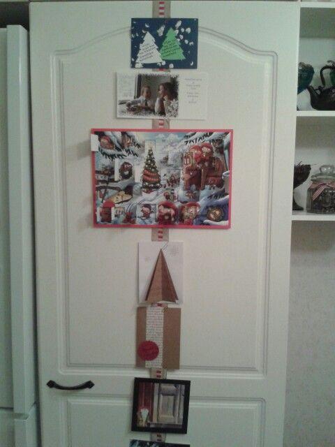 Joulukortit ja -kalenteri koristeiksi keittiönkaapin oveen