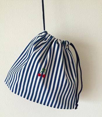 ストライプの生地でシンプルな巾着袋ですが、ワンポイントの刺繍が
