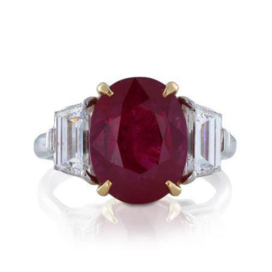 PLATINUM AND 18 KARAT YELLOW GOLD RING 3 STONE RING CONSISTING OF ONE OVAL SHAPED BURMA RUBY WEIGHING 5.45 CARATS FLANKED BY 2 STEP CUT TRAPEZOIDS WEIGHING 1.31 CARATS.    $99,000