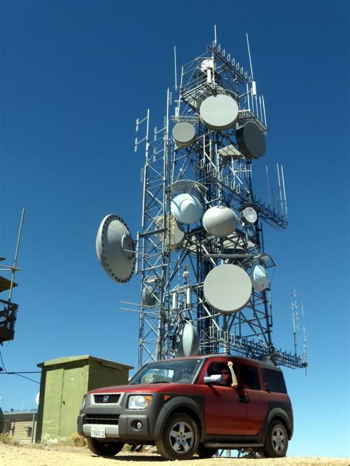 A telecommunications tower with a variety of dish antennas for