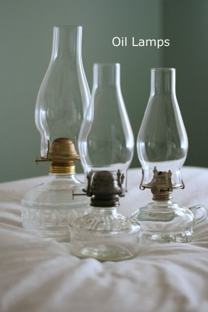 Oil lamps mixed in with clear glass bottles milk