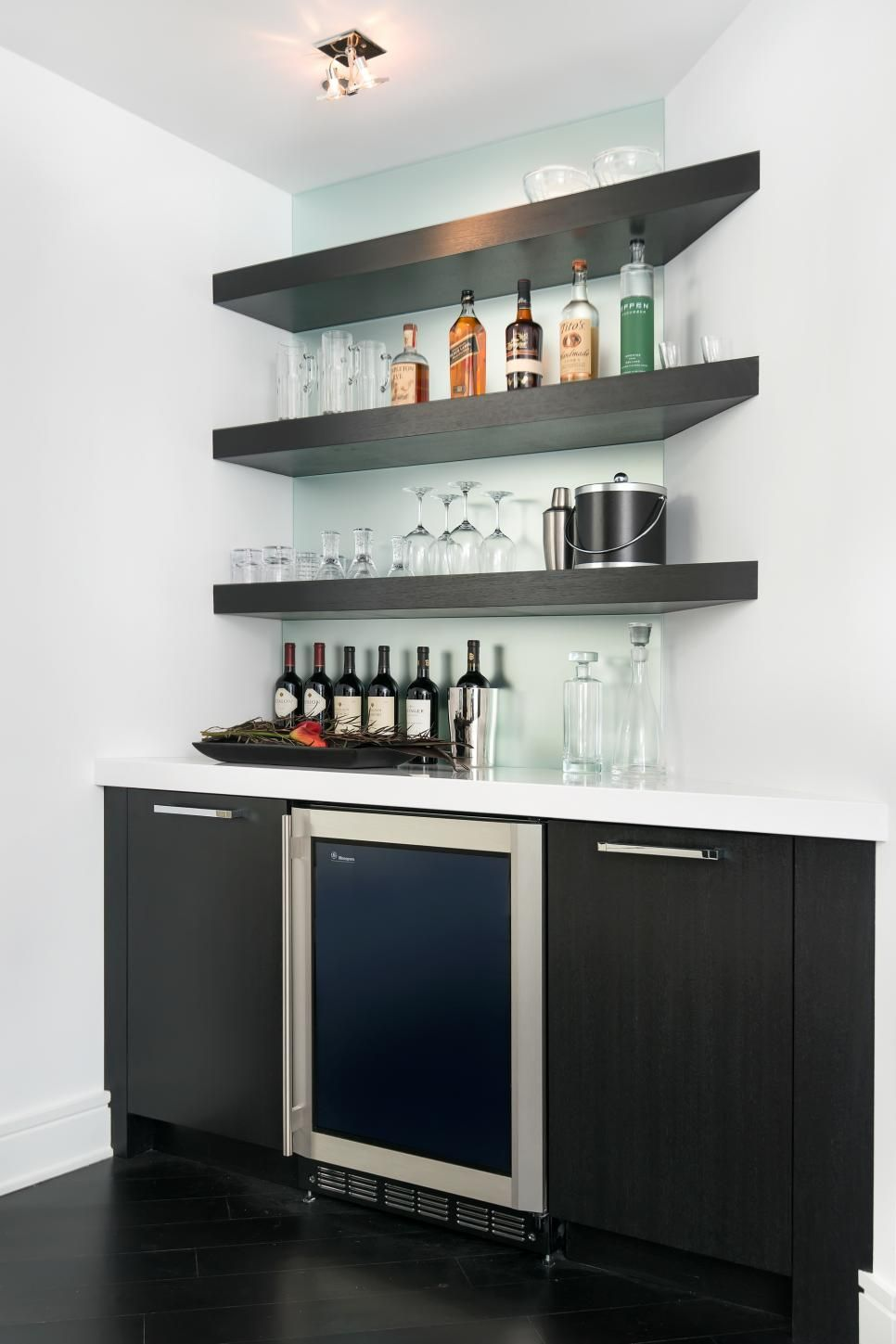 this modern wet bar features floating corner shelves and a