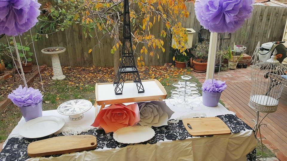 A Parisian backyard engagement set up pre cake! Custom made lace table runner and paper flowers with our Eiffel tower and pom pom stands Sarah.jane.events@outlook.com