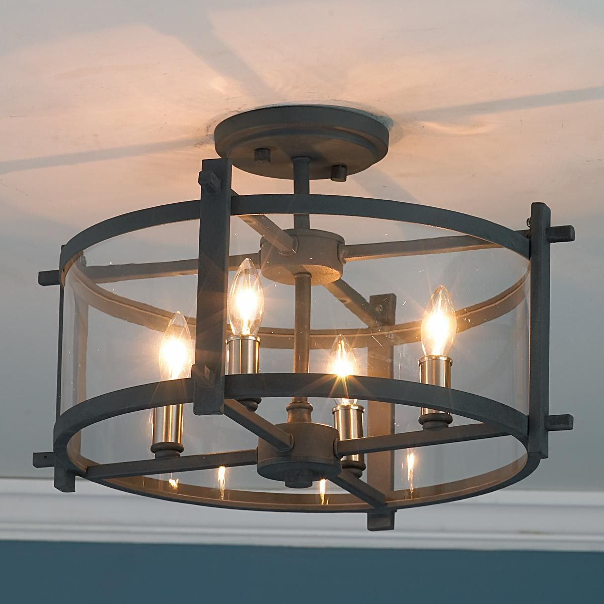 Clearly modern semi flush ceiling light clear curved glass is enclosed in dark charcoal gray iron strapping 269 4x60 watts