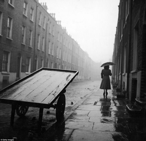A woman walks down a rainy street in post-war Whitechapel. From the Getty Images Gallery [via the Daily Mail]