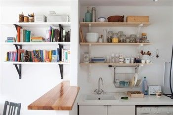 Two lots of open shelving above the sink and also with books in adjoining space