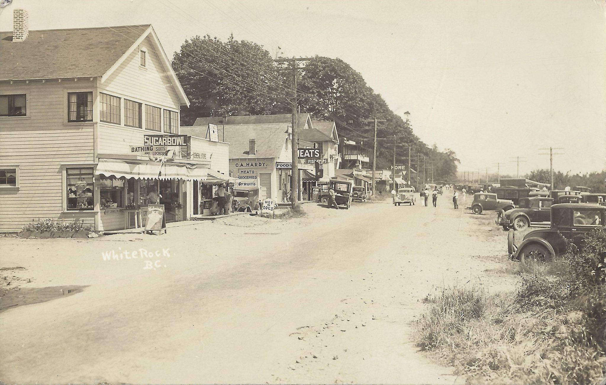 "https://flic.kr/p/Dq2px3 | c. 1935 Postcard - East End Businesses along the Waterfront / Washington Avenue at White Rock, B.C. | The first store on the left was called ""The SUGARBOWL"" looks like it was a general store selling various types of groceries and other items including  Bathing Suites and Lockers.    The next store was also a general store but I can't make out what the sign says.  Then it is C.A. HARDY MEATS / GROCERIES / FRUITS Store.  After that is a Fish & Chips Tak..."
