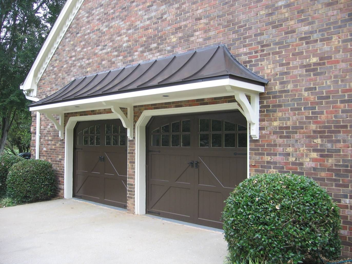 Metal roof bracket portico over double garage doors for Garage roof styles