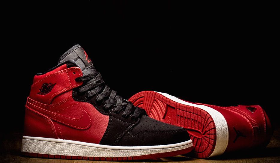 This new colorway of the Air Jordan 1 High uses red leather on the back half  of the shoe and black nubuck on the front.