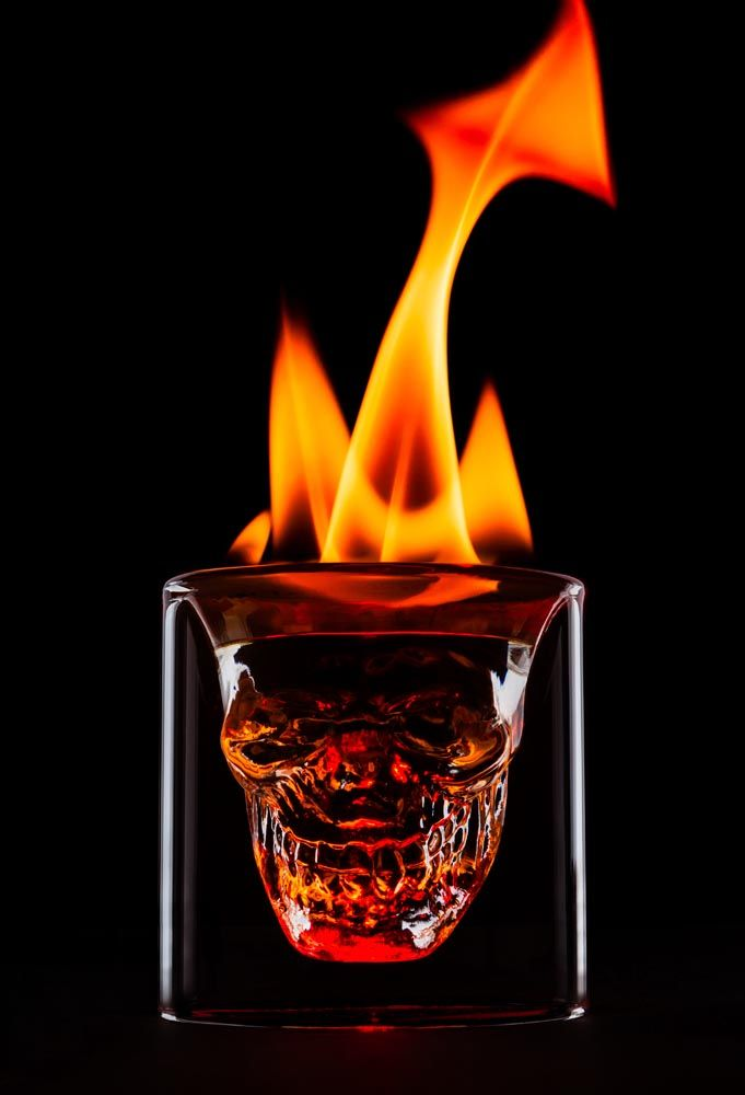 Skull shaped glass set on fire with flames in the form of horns ...
