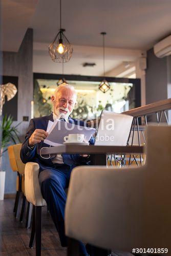 Senior businessman having phone conversation and analysing documentation