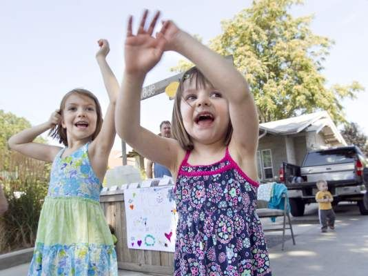 Addison Mathews, 6, and her sister Lauren, 4, wave at a passing car as they try to attract people to their lemonade stand on Barge Street in Yakima, Wash. Saturday, Aug. 3, 2013. The two were giving away lemonade, limeade, cupcakes, brownies, chocolate chip cookies and Rice Krispy treats. Still, they collected more than $20 in donations and will use it to buy supplies and pet food for The Humane Society. (GORDON KING/Yakima Herald-Republic)