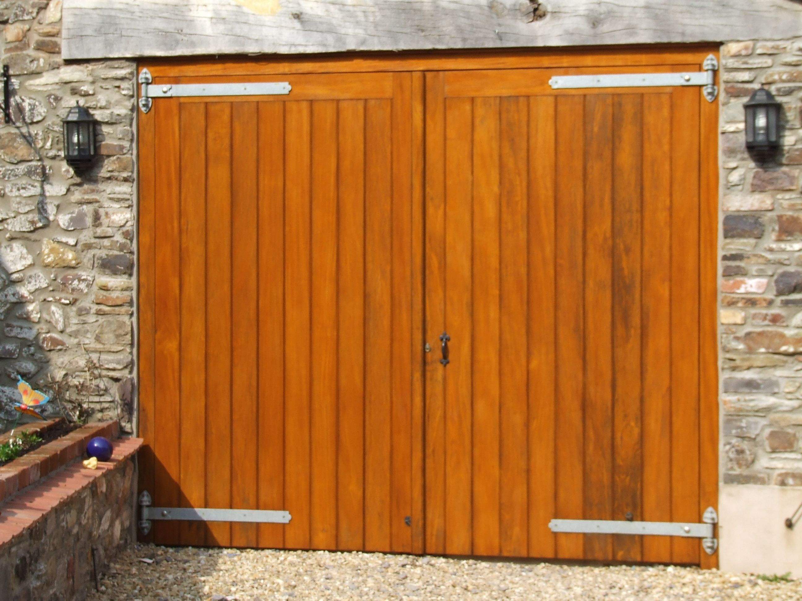 Hardwood garage doors coated with Sikkens light Oak stain and fitted with  galvanized fittings. Hardwood garage doors coated with Sikkens light Oak stain and