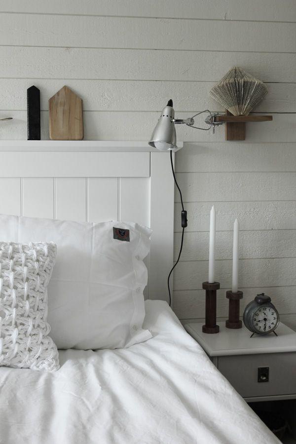 renoverat sovrum i vitt och trärent Liggande vit panel på väggen med plank Sänglampor från