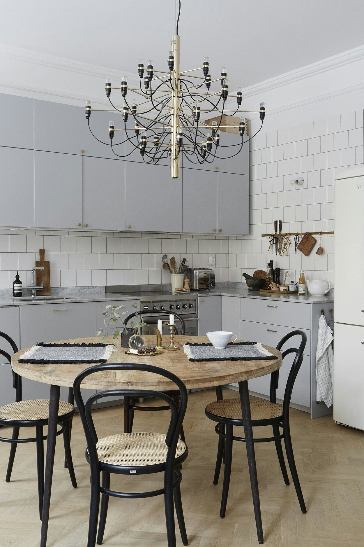 A simple modern light grey kitchen is psruced up with a gorgeous chandelier and a stylish dining set with black touches