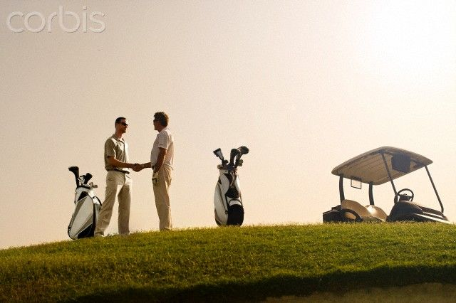 Two men on golf course at sunrise