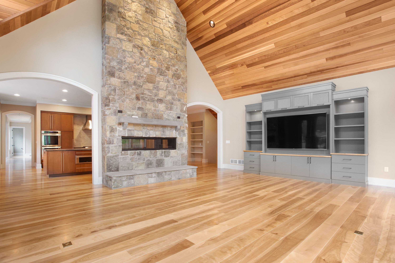 Living Room With Gray Custom Built In, Hardwood Floors, Stone Fire