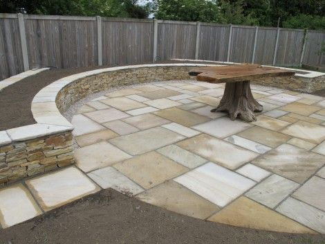 A New Quartz Stone Raised Planting Bed Under Construction Which Circumvents  A Large Sandstone Patio.