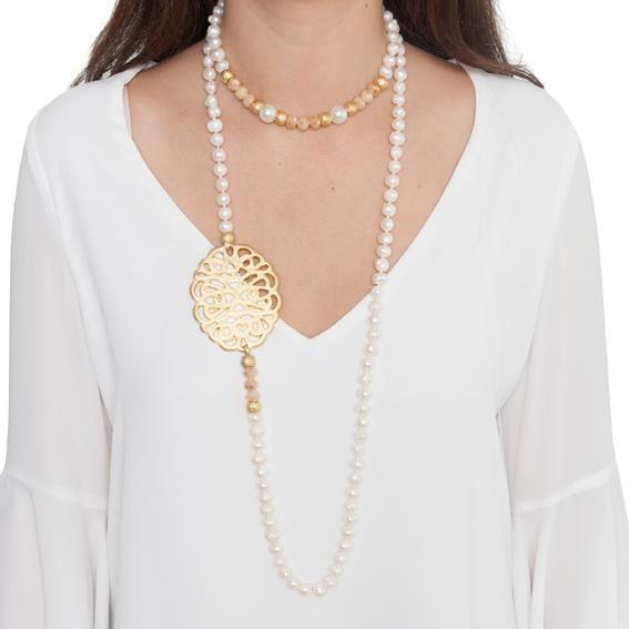 a04c0e55cb9d Collar largo de perlas de rio irregular con un medallón de rejilla bañado  en oro mate y adornado con cristal checo en colores mate y piezas en baño  de oro ...