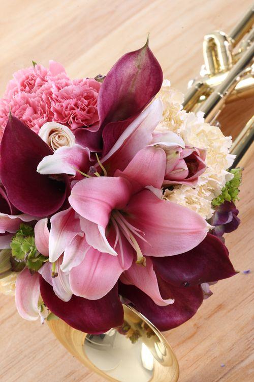 Bouquet con cartuchos ocre, rosas color crema, claveles blancos y rosados, hortensias moradas. De Floristería Celiflor.