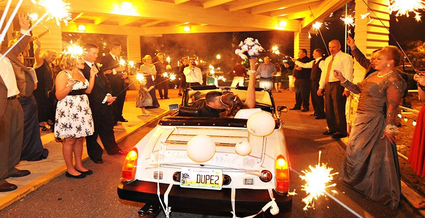 Couple getaway in a vintage car to a sparkler send off at our restaurant on the water