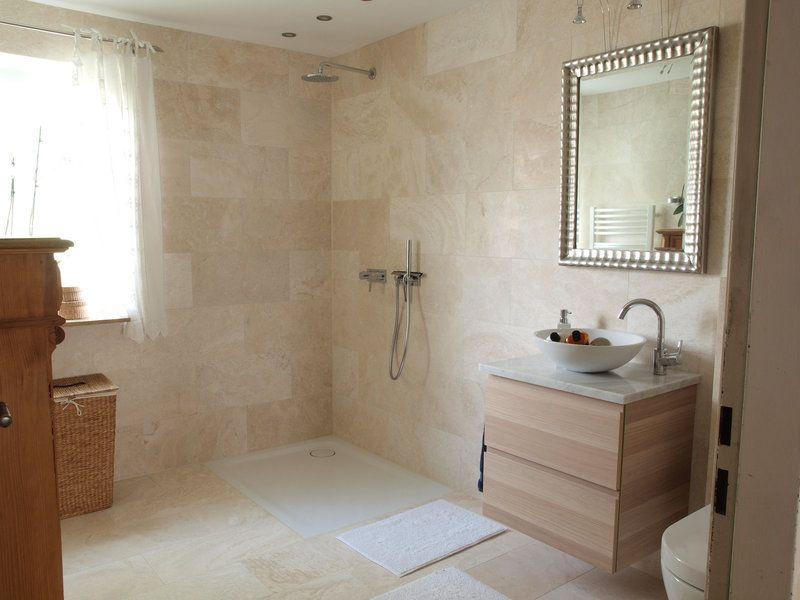 Ein zauberhaftes Duschbad das deckenhoch mit Travertin