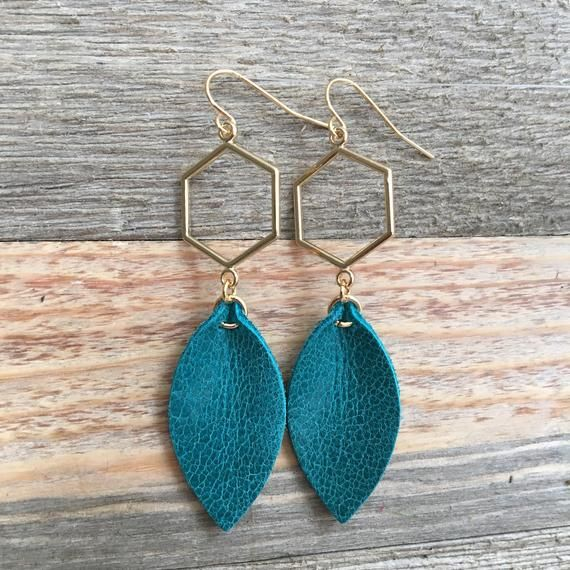 Chic and elegant turquoise leather leaf dangles from gold-tone hexagon. Glam up your daytime routine or wear them out for a night on the town. Small leather leaf is cut from turquoise sea blue and dangles from gold-tone (metal alloy) hexagon on gold-plated steel ear wires. GIFT PACKAGING:All jewelry is packaged in brown kraft gift boxes. Orders marked as gifts will include a gift receipt and option for gift message. Gift wrapping is available for an additional charge see option at checkout.PROCE