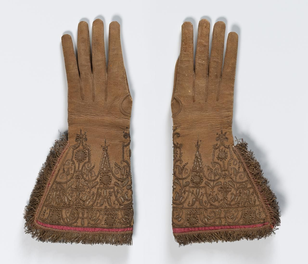 Gloves (c. 1620) (ENGLAND / THE NETHERLANDS)       Medium leather, silk (lining, thread), gilt metal (thread, fringe, spangles) Place/s of Execution (England / the Netherlands) Accession Number 1658G.a-b-D4 National Gallery of Victoria, Melbourne
