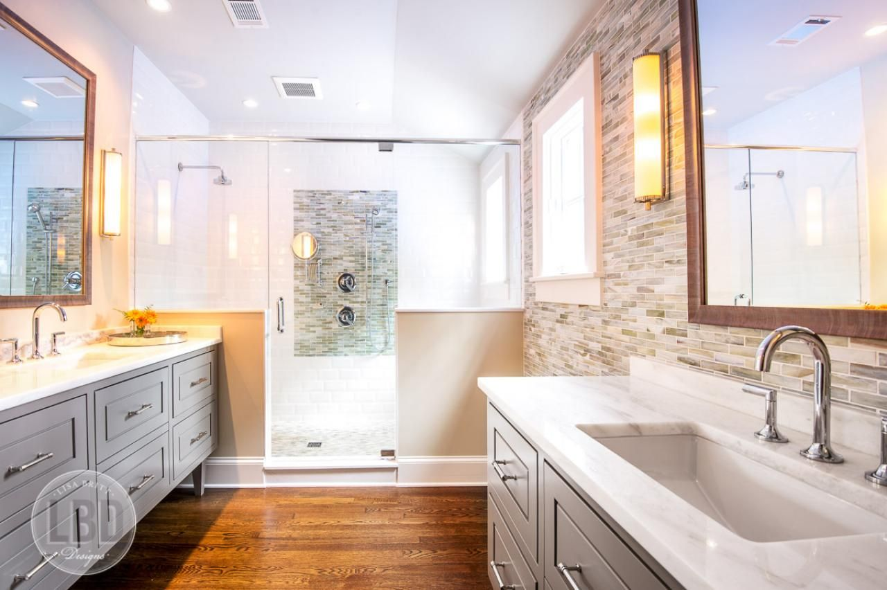 Long vanities flank opposite walls in this spacious master bathroom ...