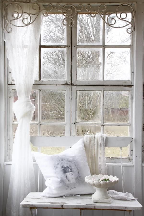 iron scrollwork framing window adds the perfect touch to this ...
