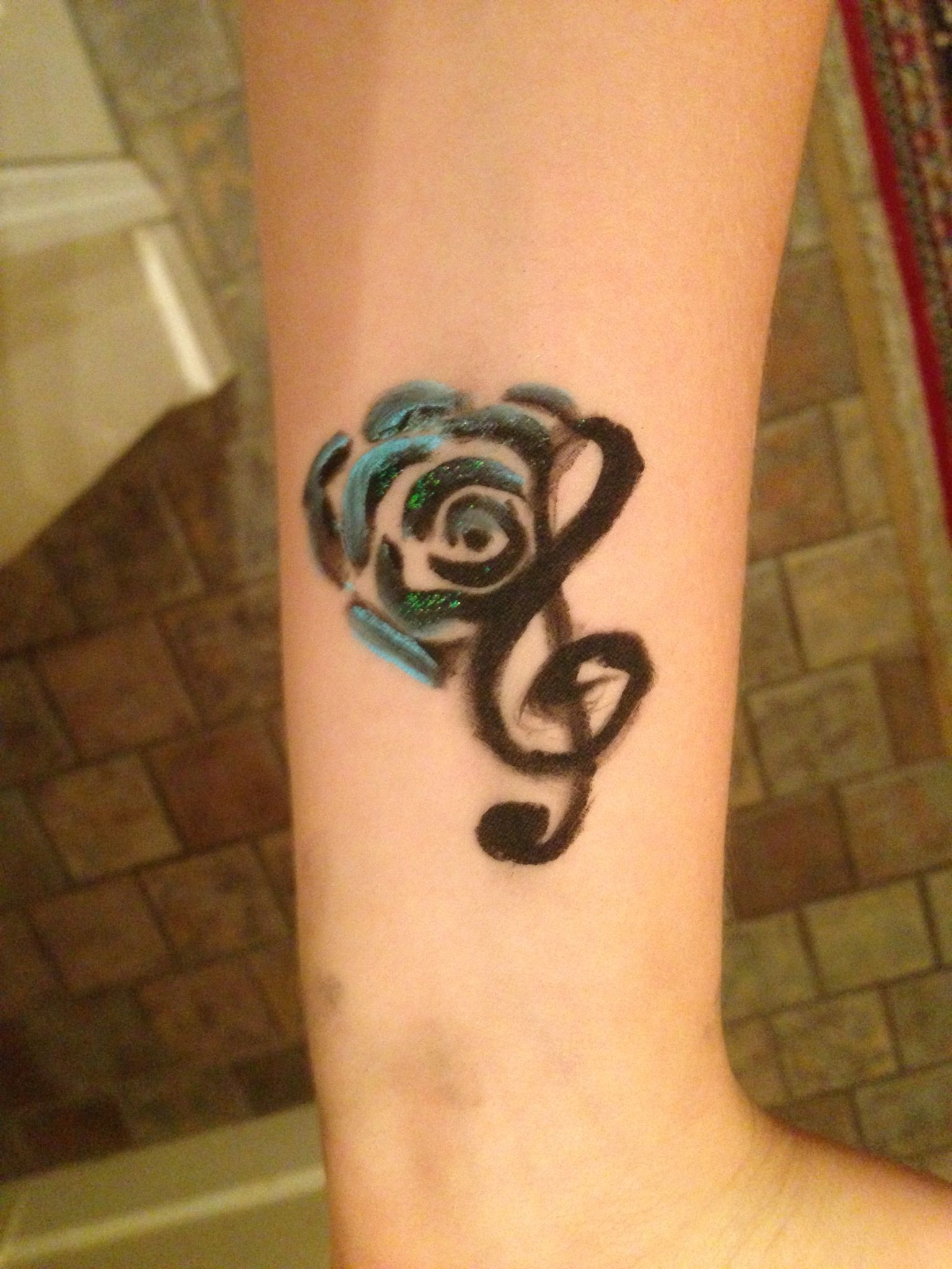 Music note & flower wrist tattoo, done in blue and glitter ...