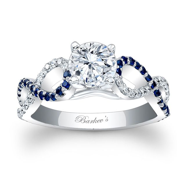 Classic and elegant this white gold blue sapphire and diamond engagement ring features a prong set round diamond center. An artfully curving cathedral shank, criss-crosses down the shoulders, adorned with shared prong set blue sapphires and diamonds for a glamorous look sure to be treasured.