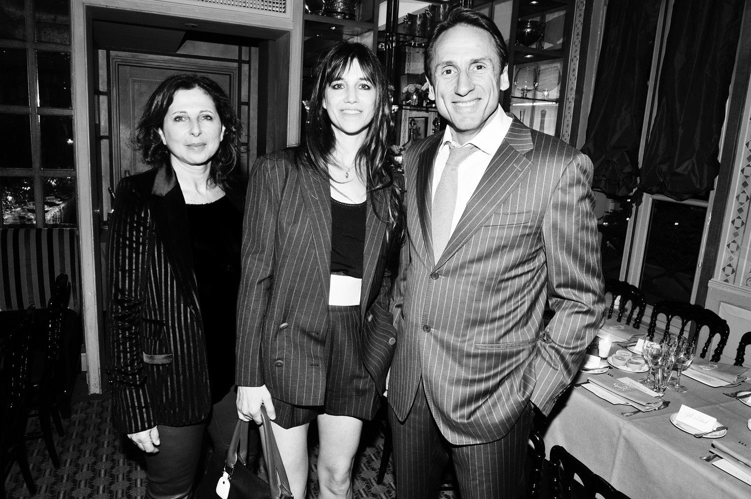 Isabelle Sarfati, Charlotte Gainsbourg (2012 ambassador) and Krishna Clough pose in Paris at a dinner to celebrate the sixth annual limited-edition bag partnership between Tommy Hilfiger and Breast Health International (BHI)