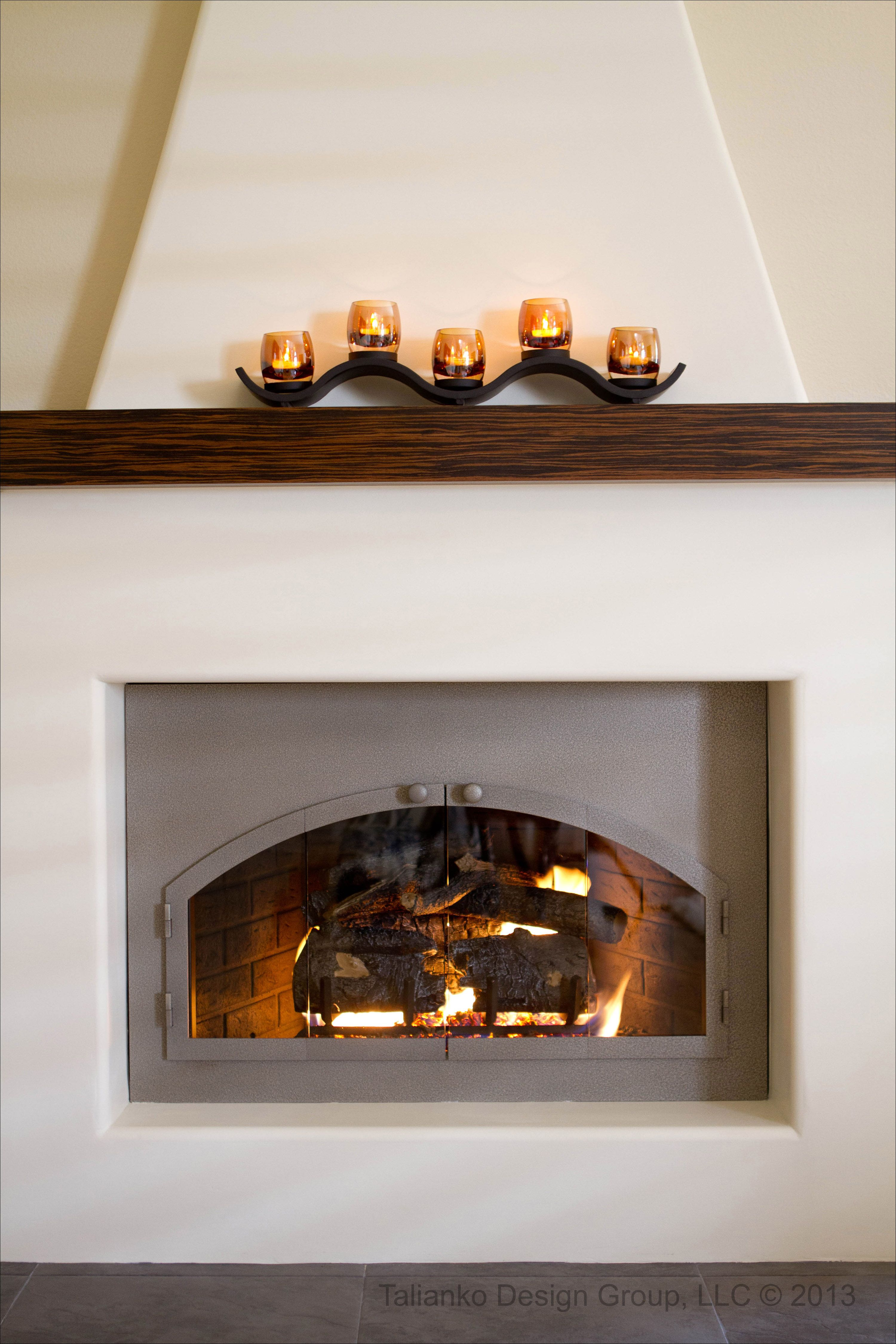 adobe inspired fireplace with a zebra wood mantle and custom iron
