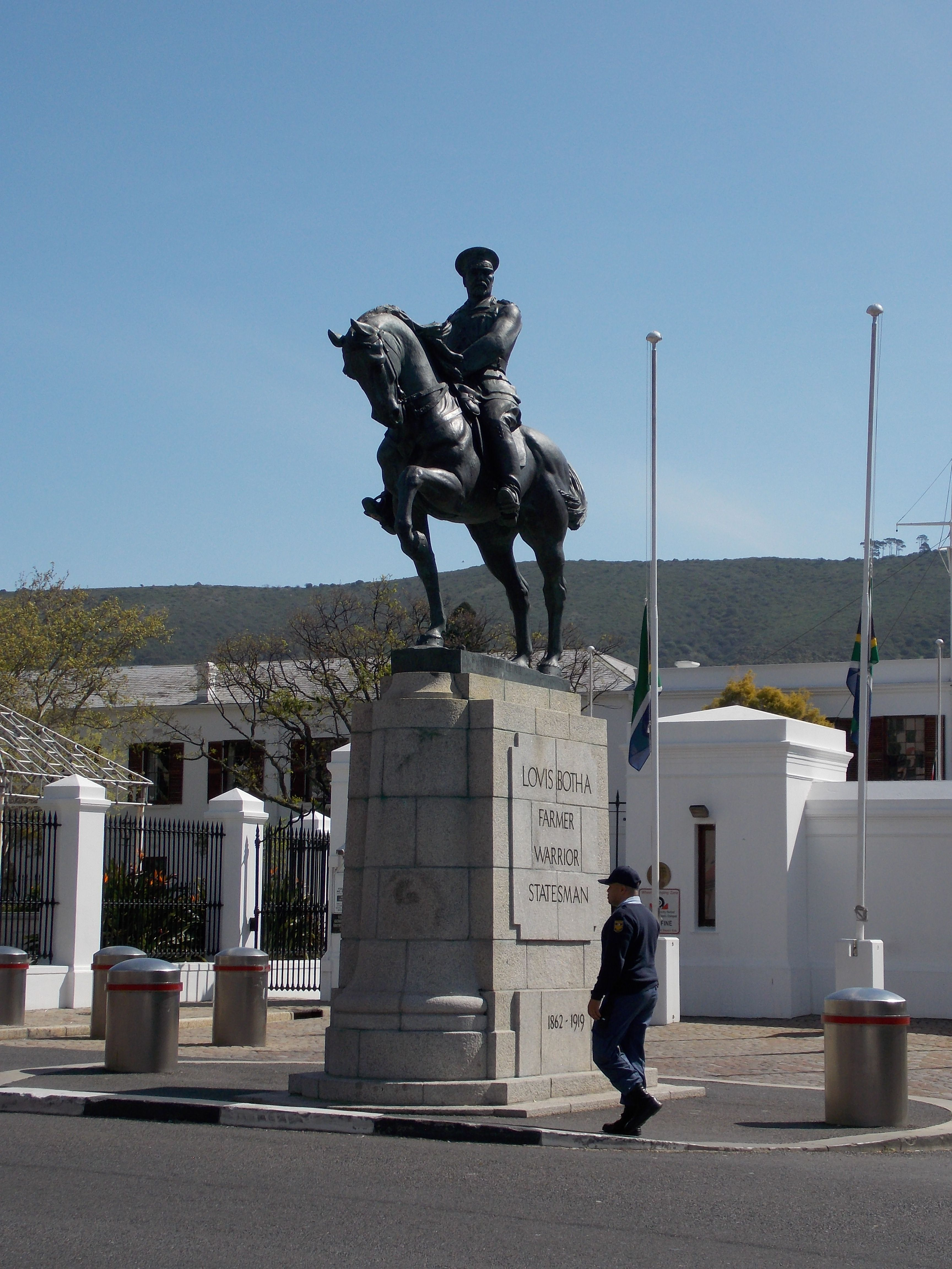 A member of the South African Police Service passes under the Botha statue at Parliament - now closely guarded, making it difficult for vandals