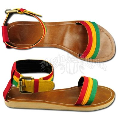 These Dub Wise rasta slip on flat sandals feature rasta colors. The open toe canvas strap is red, gold and green. The gold has a zippered look. The ankle cuff has a canvas belt buckle strap in the rasta colors with red down the back of the shoe.