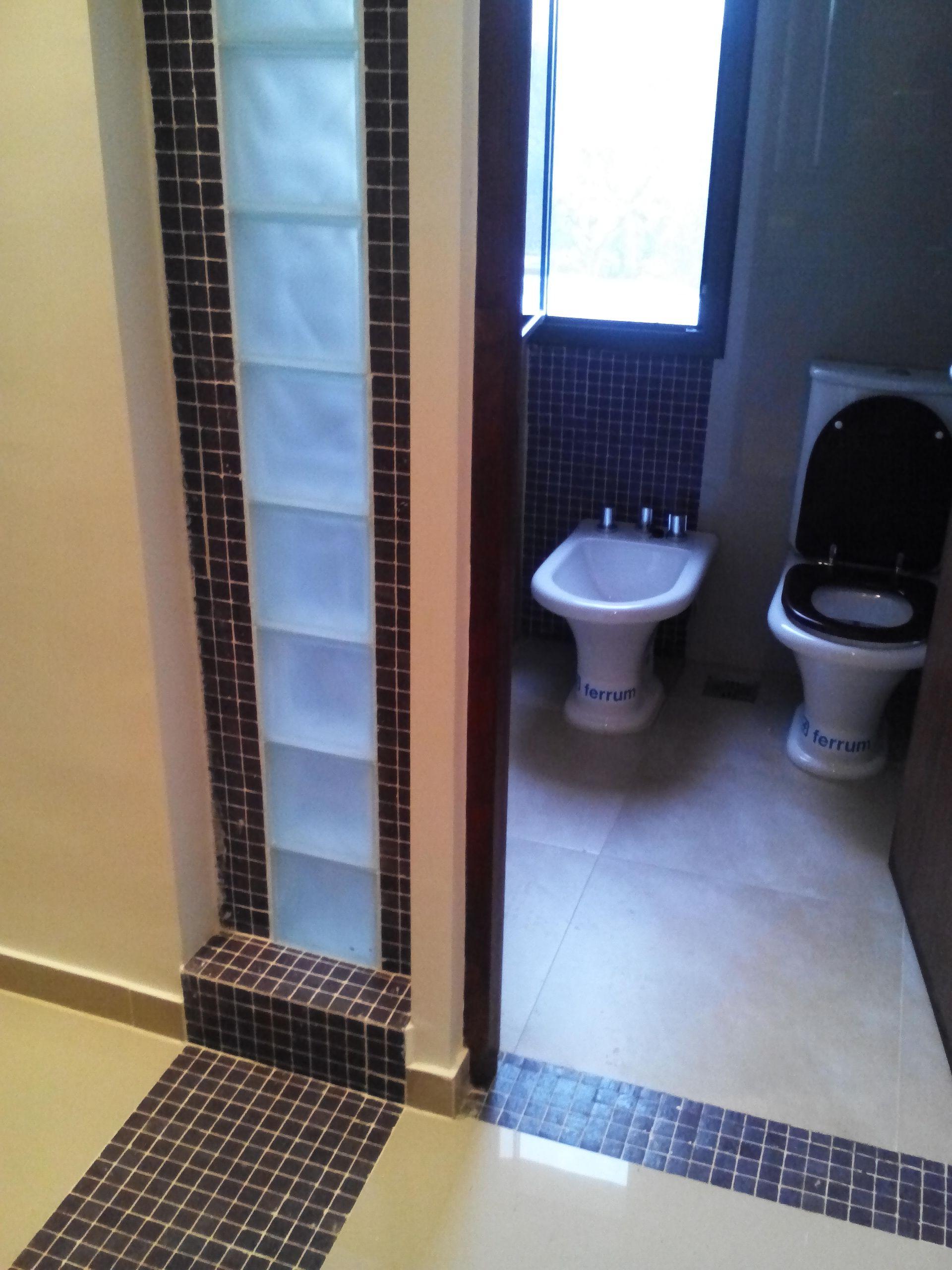 Estudio Juarez Lico   Baño: Guardas con venecitas piso pared combinadas con ladrillo de vidrio.