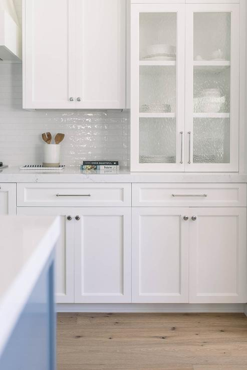 White Shaker Kitchen Cabinets Accented With Chrome Hardware And A