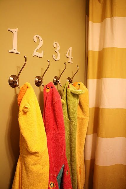 Have towel hooks at the height of your children. They can hang their own towel after bathing. Instead of numbers, how about their first initial.