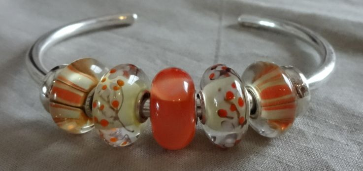 A Peach Armadillo flanked by 'Small & Beautiful' Unique Trollbeads on a silver bangle!