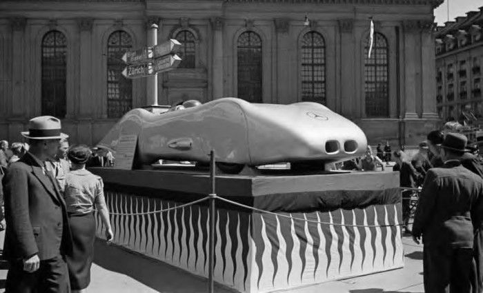 Bern Swiss GP August 1938 – Sitting on a plinth in front of the Heiliggeisit-Kirche (Church of the Holy Ghost) on the Bahnhofplatz in Bern is the 736 bhp V12 Mercedes Benz record car in which Caracciola had achieved 268 mph (436 kmh) on the Frankfurt/Darmstadt autobahn during the Rekordwoche on January 28, 1938.