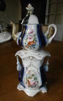 Tisanière en porcelaine de Bayeux à décor de bouquets fleuris. Prise du couvercle représentant un bouton de rose. Prise du foyer figurant une cordelière en passementerie.