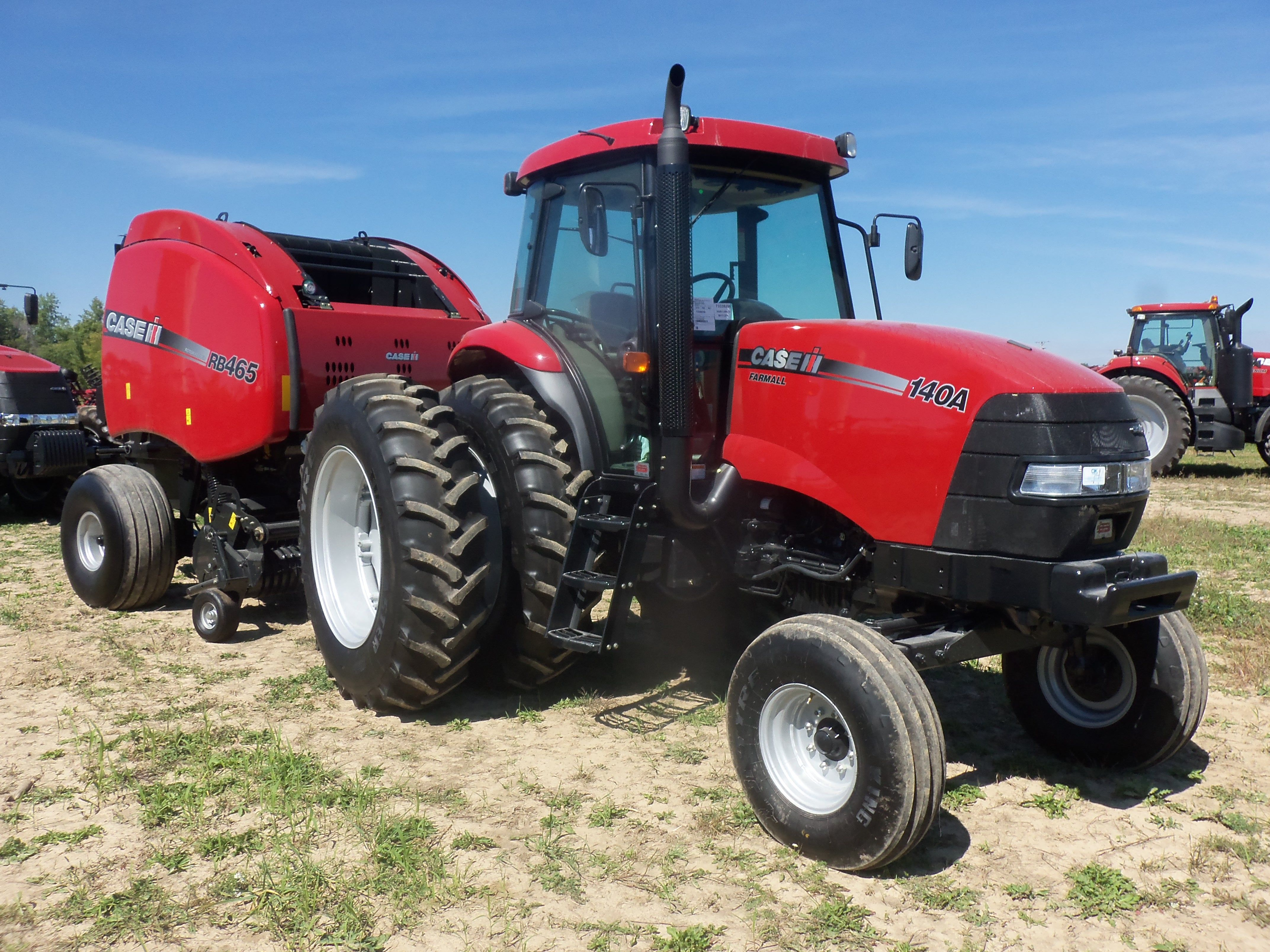 CaseIH Farmall 140A hooked to RB465 round baler | CaseIH